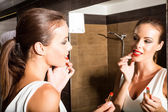Beautiful young woman putting on makeup in the bathroom	 — Stock Photo