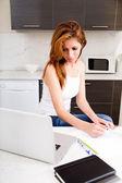 Brunette girl working in kitchen — Stock Photo