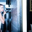 Beautiful young woman putting on makeup in the bathroom — Stock Photo #69646465