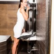 Beautiful young woman putting on makeup in the bathroom — Stock Photo #69646483