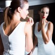 Beautiful young woman putting on makeup in the bathroom — Stock Photo #69646499