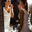 Beautiful young woman putting on makeup in the bathroom — Stock Photo #69646519