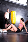 Young couple taking a break in a Gym during workout — Stock Photo
