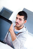 Young man with laptop in the kitchen  — Stock Photo