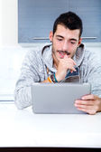 Young man with tablet in the kitchen — Stock Photo