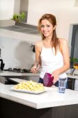 Redhead girl slicing in kitchen watching tablet pc — Stock Photo