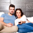 Young couple watching TV together on the Sofa — Stock Photo #75817649