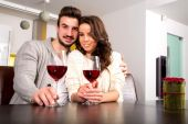 A young couple enjoying a glass of wine at home — Stock Photo