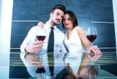 A romantic couple with a glass of wine in the dining room — Stock Photo