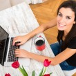 Young beautiful woman smiling while using a Laptop at home — Stock Photo #77742050