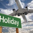 Holiday Green Road Sign and Airplane Above — Stock Photo