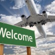 Welcome Green Road Sign and Airplane Above — Stock Photo #54417741