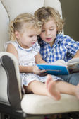 Young Brother and Sister Reading a Book Together — Foto de Stock