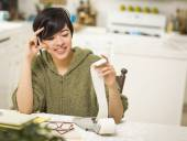 Multi-ethnic Young Woman Smiling Over Financial Calculations — Stock Photo