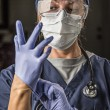 Concerned Female Doctor or Nurse Putting on Protective Facial We — Stock Photo #55934791