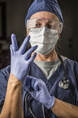 Concerned Female Doctor or Nurse Putting on Protective Facial We — Stock Photo