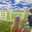 Young Family in Grass Field with Ghosted House in Front — Stock Photo #56256549