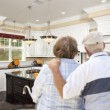Senior Couple Looking Over Beautiful Custom Kitchen — Stock Photo #56285587
