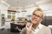 Daydreaming Woman with Pencil Inside Beautiful Custom Kitchen — Stock Photo