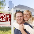Couple in Front of New House and Real Estate Sign — Stock Photo #57623965