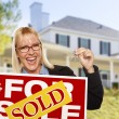 Excited Woman Holding House Keys and Sold Real Estate Sign — Stock Photo #57623977