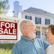 Happy Senior Couple Front of For Sale Sign and House — Stock Photo #57624023