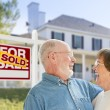 Senior Couple in Front of Sold Real Estate Sign, House — Stock Photo #57624029