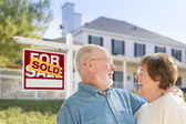 Senior Couple in Front of Sold Real Estate Sign, House — Stock fotografie