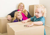 Young Family In Empty Room Playing With Moving Boxes — Stock Photo