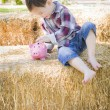 Cute Young Mixed Race Boy Putting Coins Into Piggy Bank — Stock Photo #59570169