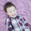Cute Young Mixed Race Boy Laughing On Picnic Blanket — Stock Photo #59570457