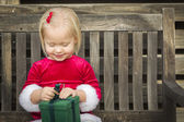Adorable Little Girl Unwrapping Her Gift on a Bench — Stock Photo