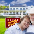 Senior Couple in Front of Sold Real Estate Sign and House — Stock Photo #62489215