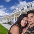 Happy Hispanic Young Couple in Front of Their New Home — Stock Photo #62821301