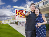 Hispanic Couple with Keys In Front of Home and Sign — Stock Photo