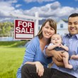 Young Family in Front of For Sale Sign and House — Stock Photo #63026335