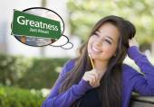 Young Woman with Thought Bubble of Greatness Green Road Sign  — Stock Photo