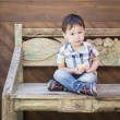 Cute Mixed Race Boy Sitting on Bench Eating Sandwich — Stock Photo #69856229