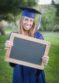 Woman Holding Diploma and Blank Chalkboard Wearing Cap and Gown — Stock Photo