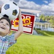 Boy Holding Ball In Front of House and Sold Sign — Stock Photo #77658090