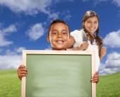 Hispânico menino e menina em campo segurando a placa de giz branco — Fotografia Stock