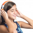 Beautiful hispanic teenage girl enjoying music on bright orange headphones — Stock Photo #51930185