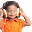 Lttle girl with an afro hairstyle enjoying her music on bright orange headphones — Stock Photo #51930329
