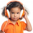 Lttle girl with an afro hairstyle enjoying her music on bright orange headphones — Stock Photo #51930331