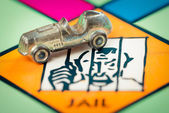 Car token next to JAIL in a Monopoly game board — Stock Photo