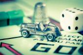 Tokens and dice next to the GO in a Monopoly board — Stock Photo