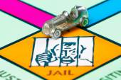 Car token next to the JAIL in a Monopoly game — Stock Photo