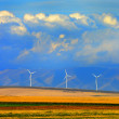 Windmills in Rows with Mountains Clouds and Fields — Stock Photo #64793917