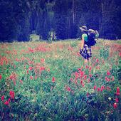Instagram stijl meisje backpacken met wilde bloemen nemen fotograaf — Stockfoto