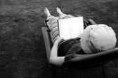 Person Lounging in Lawn Chair Relaxing and Reading Book — Stock fotografie